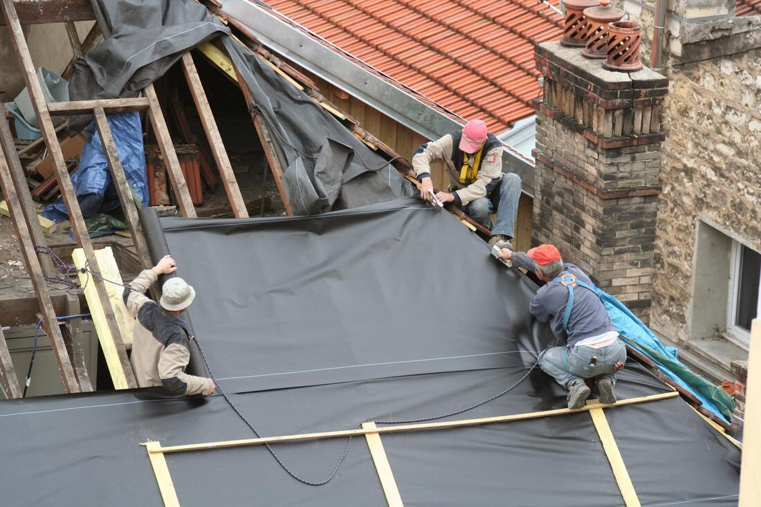 professional roofers working on house roofing